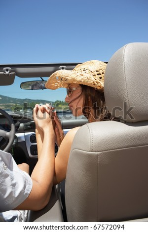 Couple holding hands in a convertible - stock photo