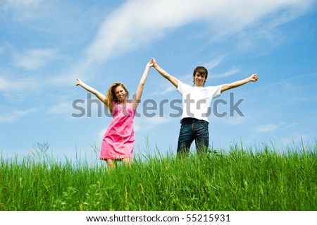 Couple holding hands in a flower field - stock photo