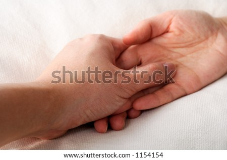 couple holding hands in bed - stock photo