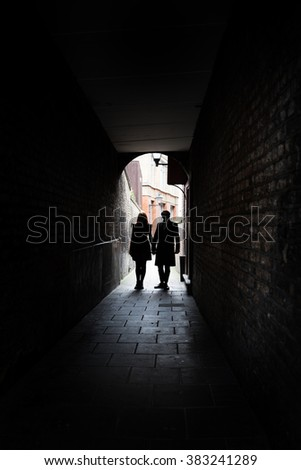 Couple holding hands in dark London alley street grimey - stock photo
