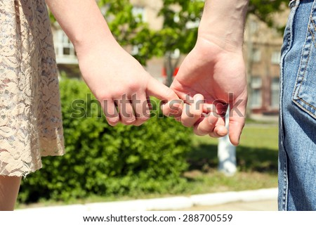 Couple holding hands on blurred background - stock photo