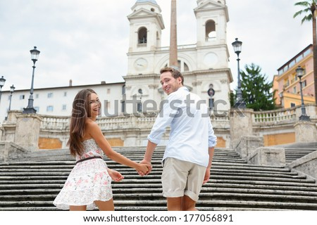 Couple holding hands on Spanish Steps, Rome, Italy. Happy romantic couple. Young interracial couple walking on the travel landmark tourist attraction icon during their romance Europe holiday vacation - stock photo