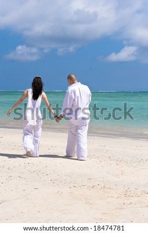 couple holding hands on the beach - stock photo