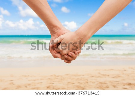 Couple holding hands on the beach. - stock photo