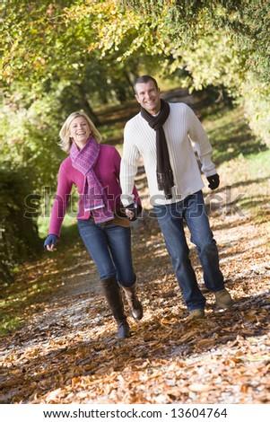 Couple holding hands on walk through autumn woods - stock photo