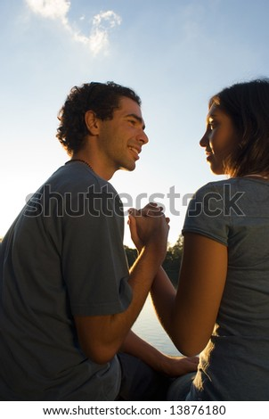 Couple Holding Hands under a Blue Sky while they look at each other happily. Vertically framed photograph.