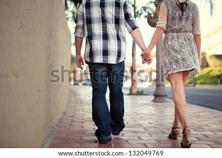 Couple Holding Hands Walking Away - stock photo