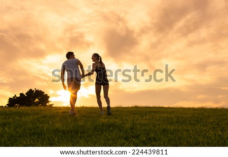 Couple holding hands walking away - stock photo