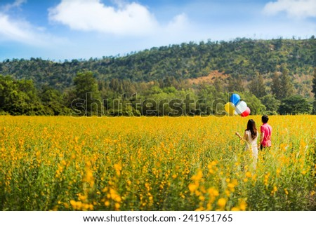 Couple holding hands walking into a garden flower girl holding balloons - stock photo