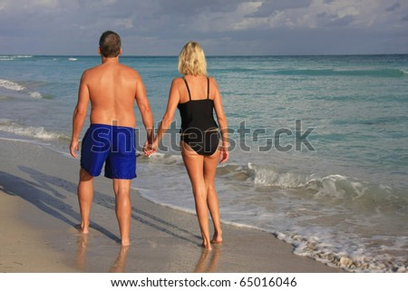Couple holding hands, walking on the beach. - stock photo