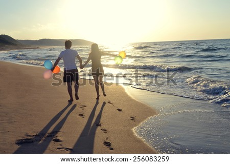 Couple holding hands walking romantic on beach on vacation travel holidays leaving footprints in the sand