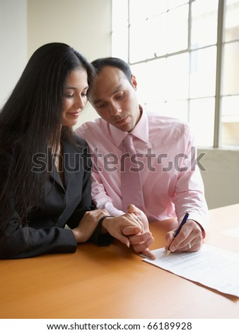 Couple holding hands while signing a document - stock photo