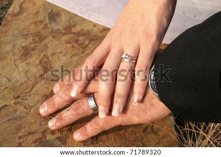 Couple holding hands with wedding rings against limestone background