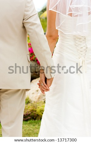 Couple holding hands with wedding rings (just married) - stock photo