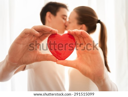 Couple holding heart while kissing. - stock photo