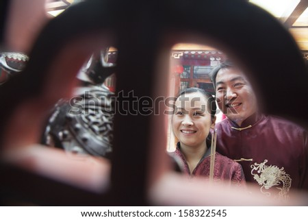 Couple holding incense at temple in traditional clothing - stock photo