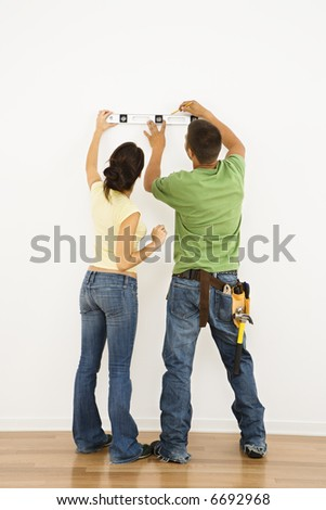 Couple holding level to interior wall and marking with pencil. - stock photo