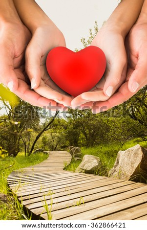 Couple holding miniature heart in hands against wooden trail across countryside - stock photo