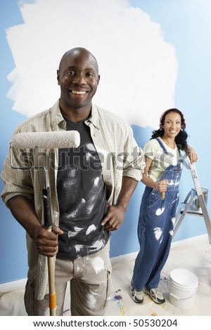 Couple holding paint rollers, portrait, elevated view - stock photo