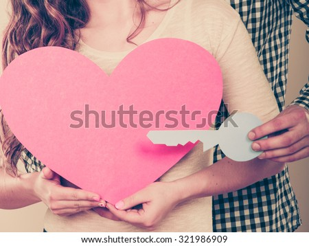 Couple holding paper key to heart sign love symbol. Loving husband and wife dreaming about new home. Instagram filter. - stock photo