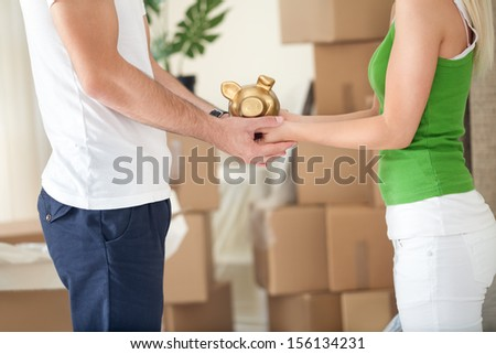 Couple holding piggy bank in their new home  - stock photo