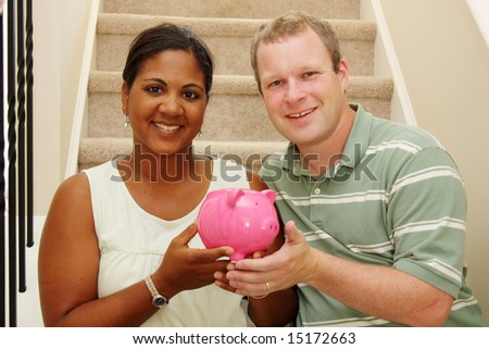 Couple Holding Piggy Bank With Their Savings - stock photo