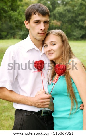 couple holding red heart on a stick - stock photo
