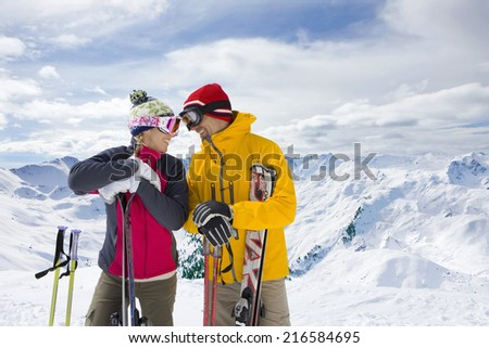 Couple holding skis standing on mountain top together - stock photo