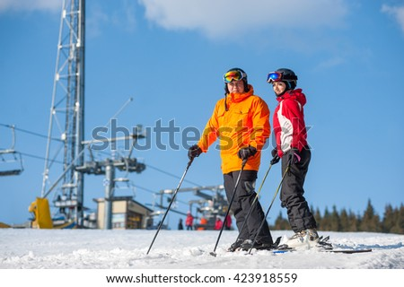 Couple holding skis standing on mountain top together with ski lifts and blue sky in background. Man is wearing orange jacket, female in red jacket, both is wearing helmet and goggles.