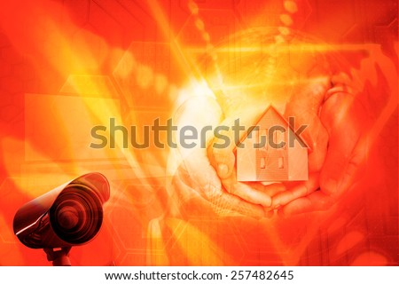 Couple holding small model house in hands against black background with shiny hexagons - stock photo