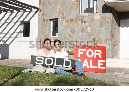 Couple holding sold sign and keys against their new house