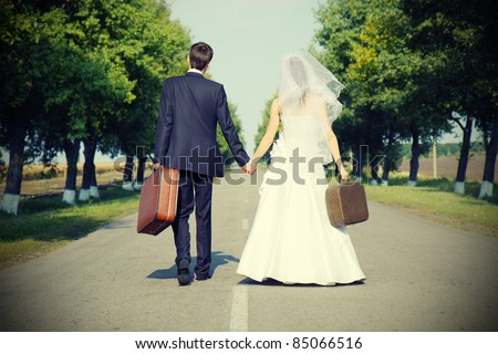 couple holding suitcases  on countryside road - stock photo
