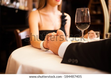 Couple holding their hands in a restaurant - stock photo