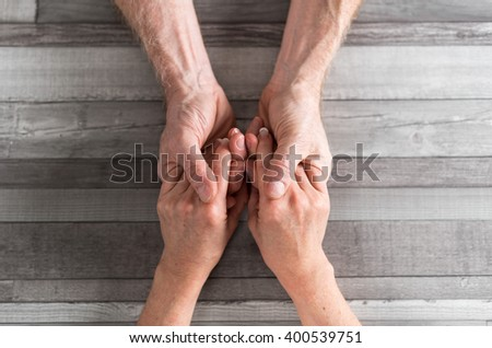 Couple holding their hands on wooden background