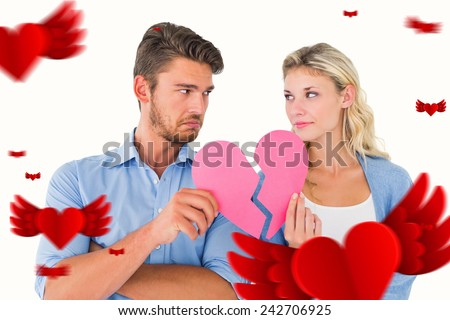 Couple holding two halves of broken heart against hearts - stock photo