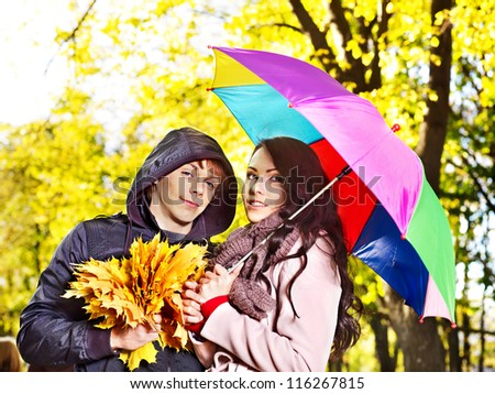 Couple holding umbrella  autumn outdoor. - stock photo