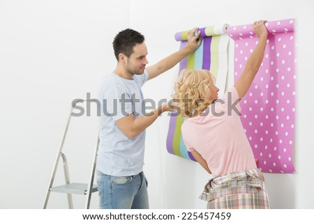 Couple holding up wallpaper samples in new house - stock photo