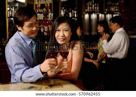 Couple holding wine glasses, woman looking at camera