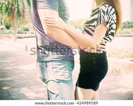 Couple hugging and cuddling each other in public park. - stock photo