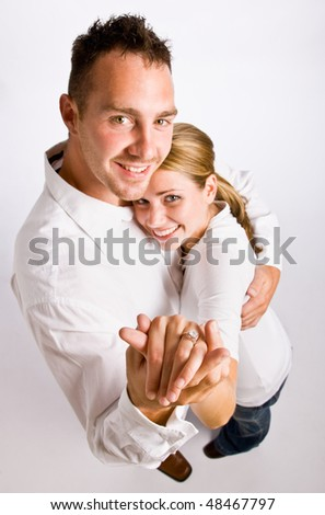 Couple hugging and displaying engagement ring