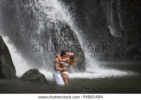 Couple hugging and kissing under waterfalls. - stock photo