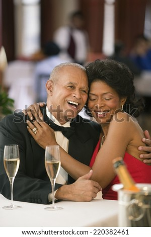 Couple hugging and laughing at dinner table - stock photo