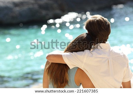 Couple hugging and watching the turquoise sea on holidays in a tropical beach - stock photo