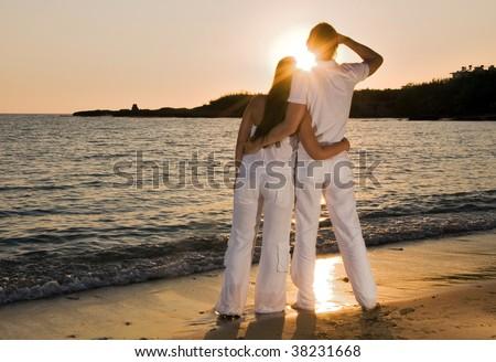 Couple hugging, enjoying summer sunset. - stock photo