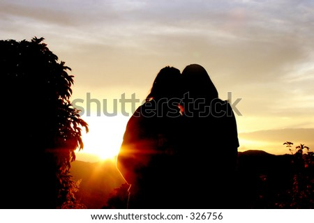 couple hugging in front of a sunset - stock photo