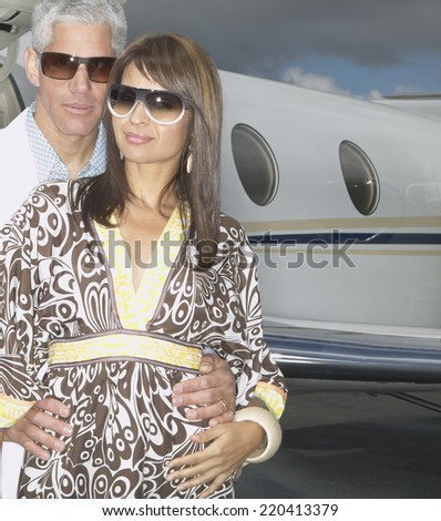 Couple hugging in front of small jet - stock photo