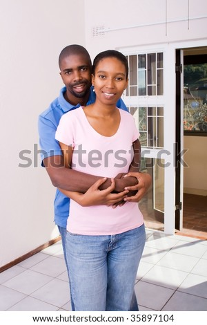 couple hugging in new home - stock photo