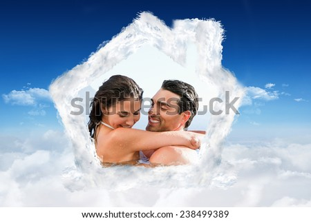 Couple hugging in the pool against bright blue sky over clouds - stock photo