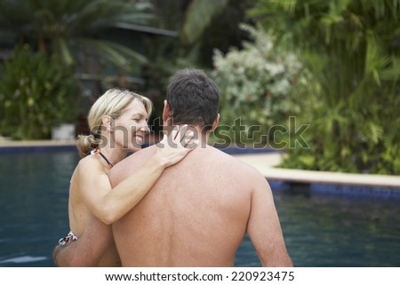 Couple hugging next to swimming pool