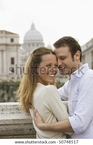 Couple hugging on bridge in Rom, Italy, side view